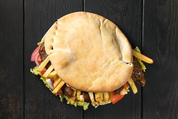 Vista superior do pão pitta recheado com salada, tomate, cebola, batata frita e cordeiro