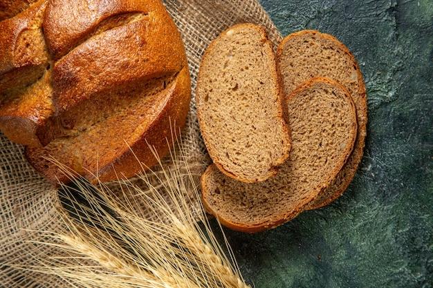 Vista superior do pão preto dietético inteiro e cortado e espinhos na toalha marrom na superfície de cores escuras