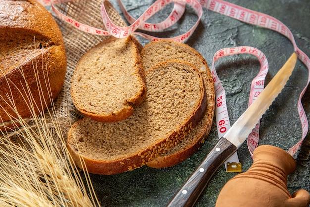 Vista superior do pão preto dietético inteiro e cortado e espinhos no medidor de toalha marrom na superfície de cores escuras