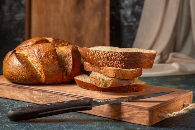 Vista superior do pão preto inteiro e cortado em uma tábua de madeira marrom na superfície escura