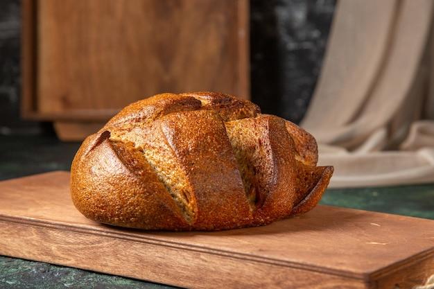 Vista superior do pão preto inteiro em uma tábua de madeira marrom em uma superfície de cores escuras