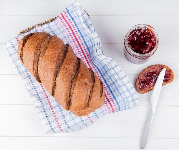 Vista superior do pão preto no pano xadrez com geléia manchada no pedaço de pão de centeio e faca na mesa de madeira