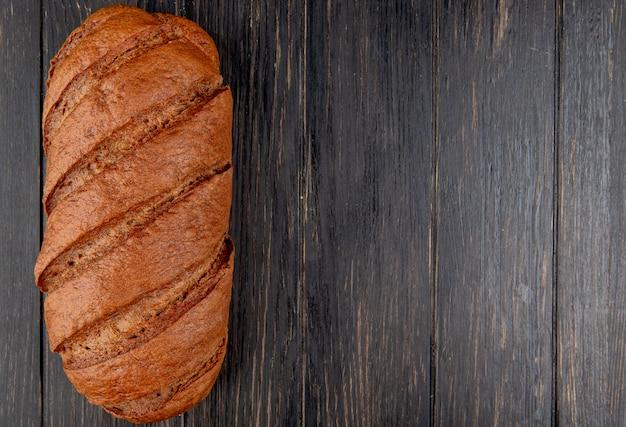 Vista superior do pão preto sobre fundo de madeira com espaço de cópia