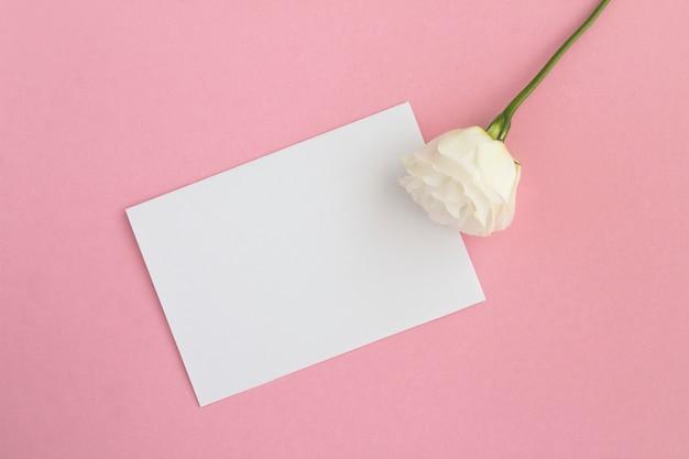 Vista superior do papel branco vazio para texto e flor branca no fundo rosa
