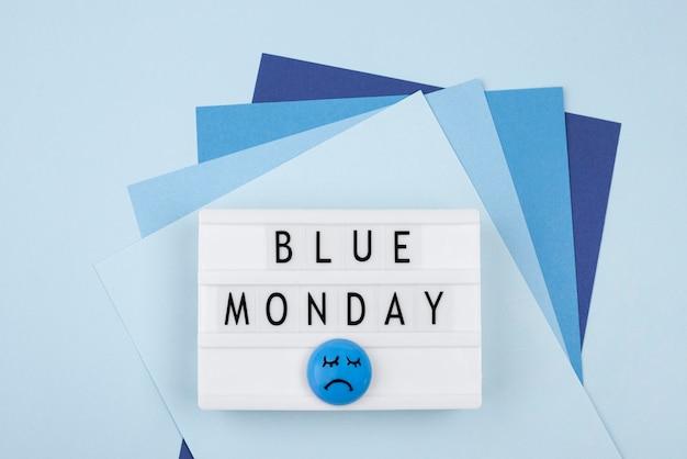 Vista superior do papel com rosto triste e caixa de luz para segunda-feira azul