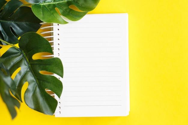 Vista superior do papel de nota em branco e da folha de monstera em fundo amarelo