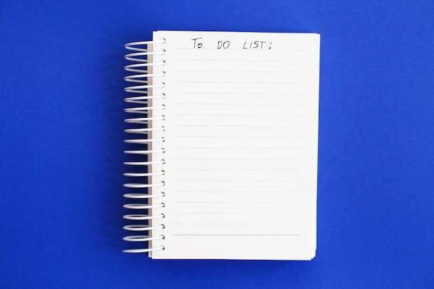 Vista superior do papel de nota em branco sobre fundo azul para fazer a lista
