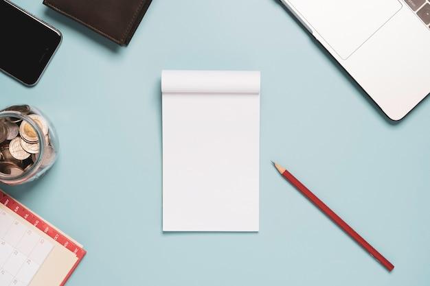 Vista superior do papel em branco branco com laptop lápis vermelho e dinheiro na mesa de fundo azul.