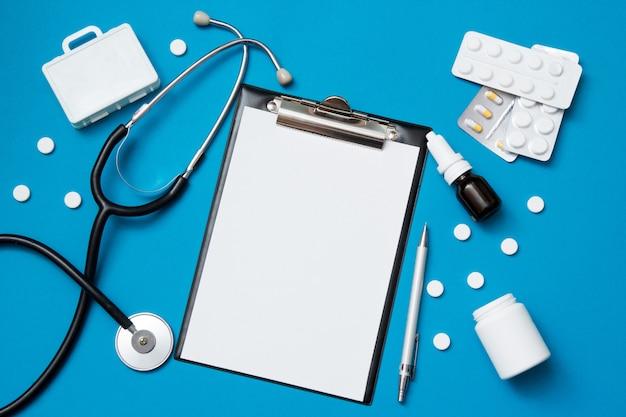 Vista superior do papel em branco para escrever a prescrição médica com estetoscópio. comprimidos em fundo azul.