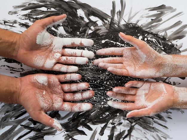 Vista superior do par de mãos cobertas de tinta branca