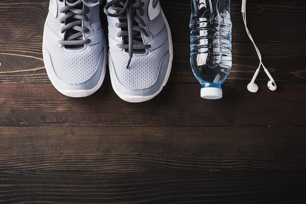 Vista superior do par de tênis esportivos, fones de ouvido e garrafa de água na mesa de madeira preta