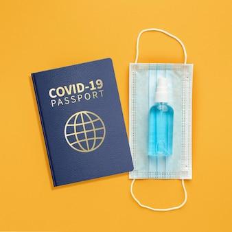 Vista superior do passaporte de saúde com máscara médica e desinfetante para as mãos
