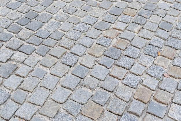 Vista superior do pavimento de pedra velho cinza ou estrada de paralelepípedos de granito