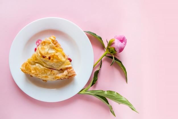 Vista superior do pedaço de torta de cereja com flores peônias em um fundo rosa