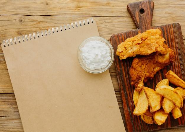 Vista superior do peixe com batatas fritas com caderno e molho