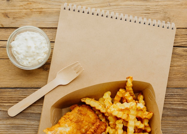 Vista superior do peixe com batatas fritas com molho e caderno