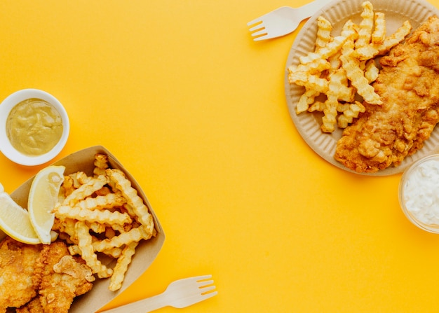 Vista superior do peixe com batatas fritas com molhos e garfos