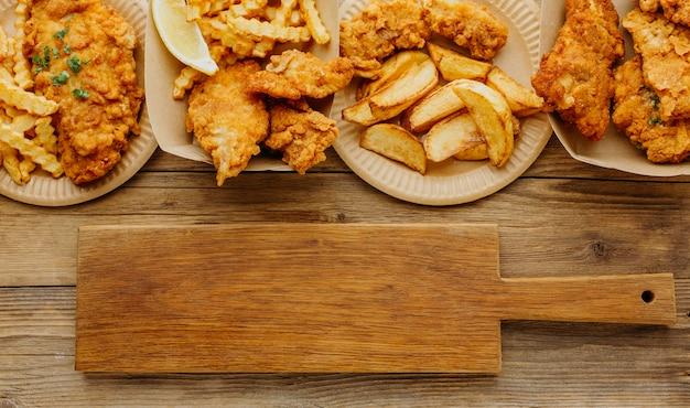 Vista superior do peixe com batatas fritas com tábua de cortar