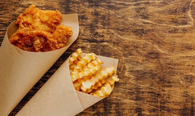 Vista superior do peixe com batatas fritas em papel de embrulho com espaço de cópia