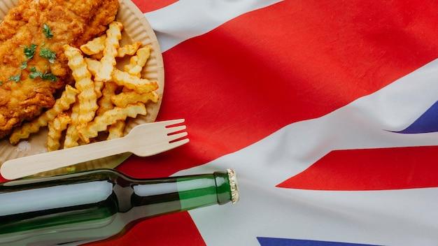 Vista superior do peixe com batatas fritas no prato com a garrafa de cerveja e a bandeira da grã-bretanha