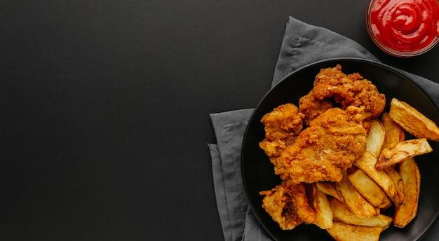 Vista superior do peixe com batatas fritas no prato com espaço de cópia