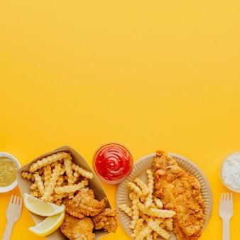 Vista superior do peixe e batatas fritas com vários molhos e espaço de cópia
