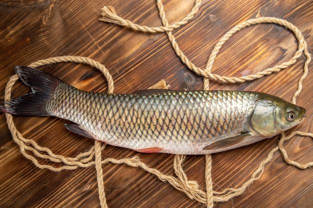 Vista superior do peixe fresco com cordas na mesa de madeira