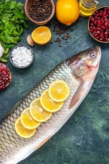Vista superior do peixe fresco com rodelas de limão na mesa da cozinha