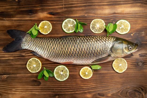 Vista superior do peixe fresco com rodelas de limão na mesa de madeira