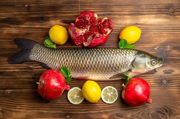 Vista superior do peixe fresco com romãs e limão na mesa de madeira