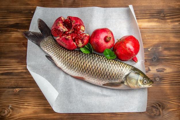 Vista superior do peixe fresco com romãs na mesa de madeira