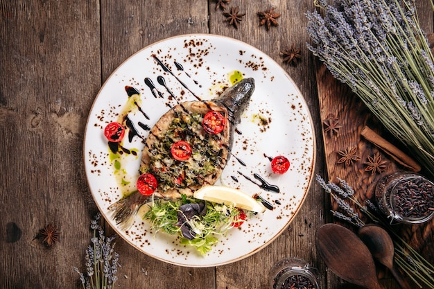 Vista superior do peixe grelhado recheado na mesa de madeira