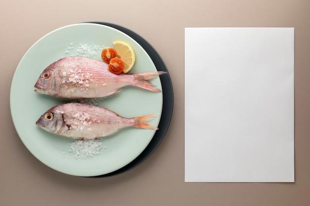 Vista superior do peixe no prato com tomate e papel