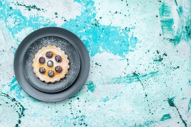 Vista superior do pequeno bolo com açúcar em pó e cerejas dentro do prato em azul claro, torta de bolo de frutas