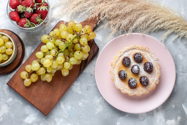 Vista superior do pequeno bolo com frutas de açúcar em pó junto com morangos vermelhos frescos e uvas na luz, bolo de frutas asse chá doce