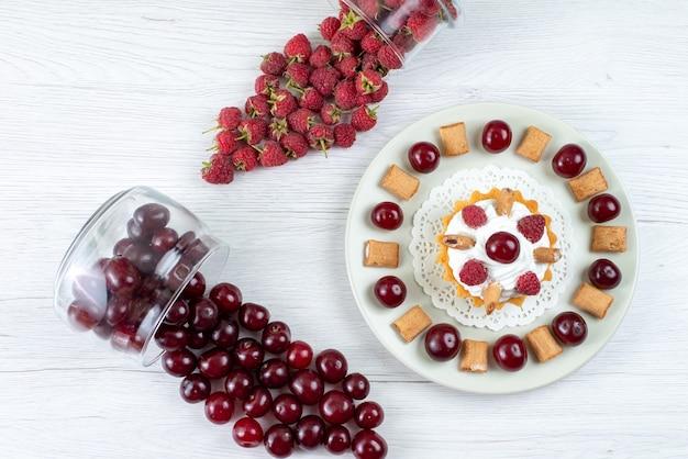 Vista superior do pequeno bolo cremoso com cerejas ácidas e framboesas na mesa branca clara bolo de frutas frescas doce de frutas frescas