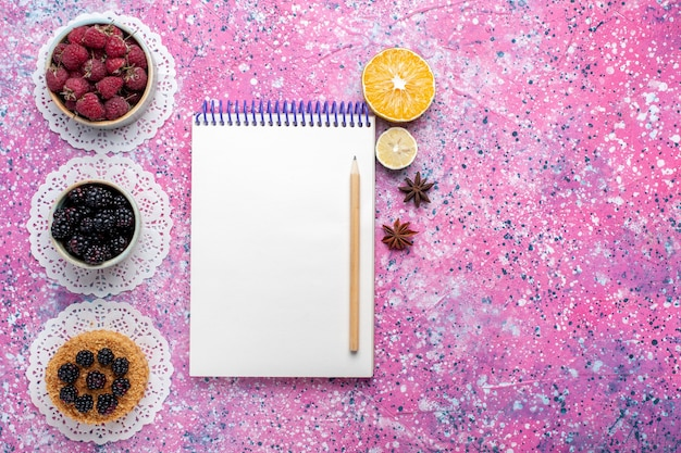 Vista superior do pequeno bolo de amora com framboesas frescas e amoras na superfície rosa claro