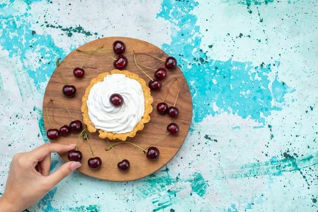 Vista superior do pequeno bolo de creme com cerejas frescas em fundo azul claro bolo creme fruta assar doce