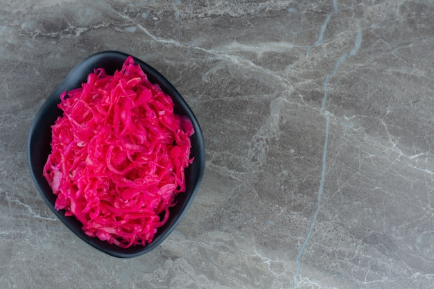 Vista superior do pickle de repolho rosa em tigela preta.