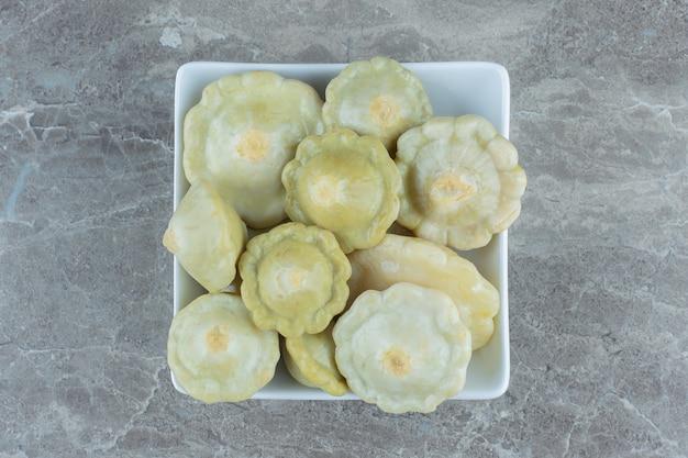 Vista superior do pickle verde patty pan squash em uma tigela branca.