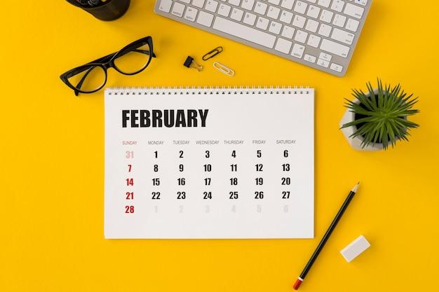 Vista superior do planejador, calendário e planta de fevereiro