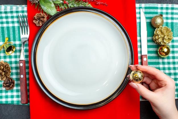 Vista superior do plano de fundo da refeição de natal nacional com talheres de pratos vazios segurando um dos acessórios de decoração na toalha verde despojada
