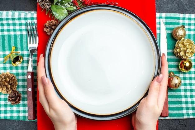 Vista superior do plano de fundo da refeição natalina nacional com a mão segurando os talheres de pratos vazios e acessórios de decoração em toalha verde despojada