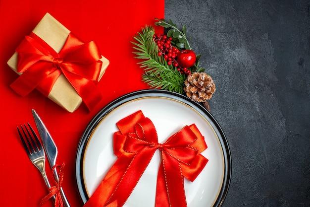 Vista superior do plano de fundo de ano novo com fita vermelha no prato de jantar talheres acessórios de decoração ramos de abeto ao lado de um presente em um guardanapo vermelho em uma mesa preta
