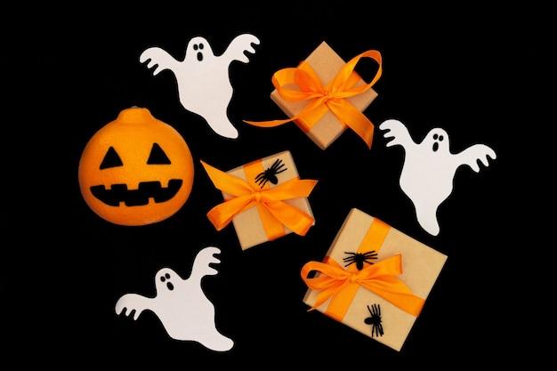 Vista superior do plano de fundo de halloween. caixas de presentes, aranhas, fantasmas de papel e cabeça de macaco laranja