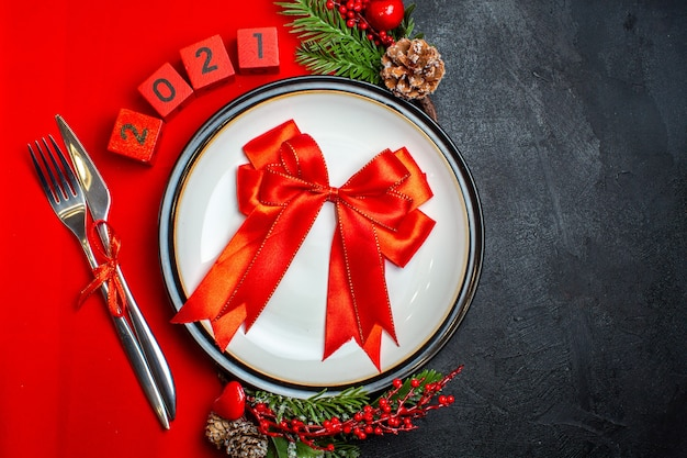 Vista superior do plano de fundo do ano novo com fita vermelha no prato de jantar talheres acessórios de decoração ramos de abeto e números em um guardanapo vermelho sobre uma mesa preta