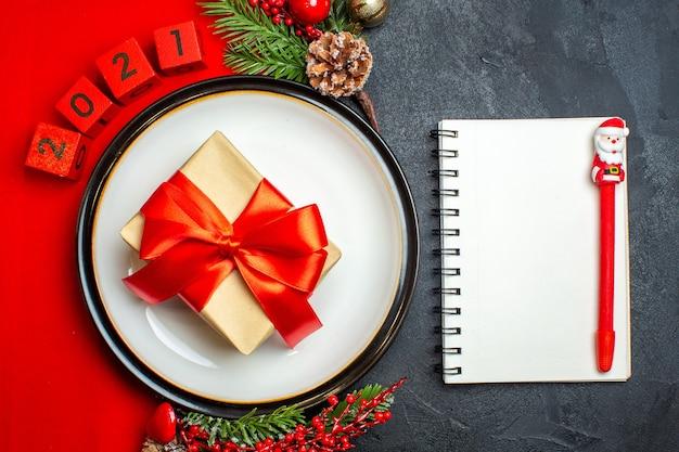 Vista superior do plano de fundo do ano novo com o presente no prato de jantar acessórios de decoração ramos de abeto e números em um guardanapo vermelho e caderno com caneta em uma mesa preta