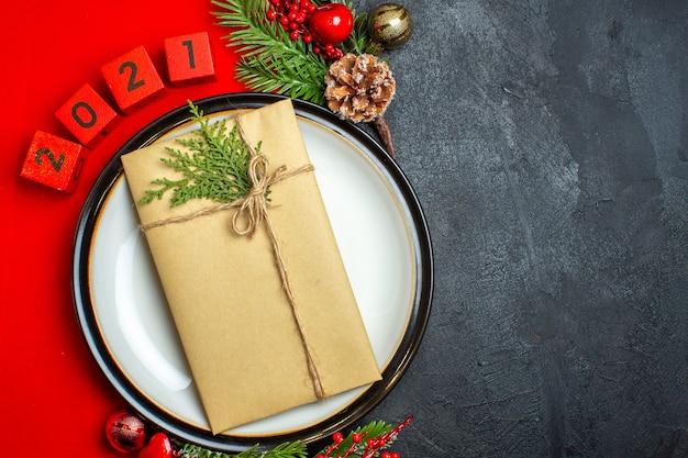 Vista superior do plano de fundo do ano novo com o presente no prato de jantar acessórios de decoração ramos de abeto e números em um guardanapo vermelho no lado direito em uma mesa preta