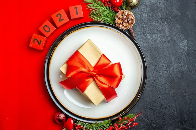 Vista superior do plano de fundo do ano novo com o presente no prato de jantar acessórios de decoração ramos de abeto e números em um guardanapo vermelho sobre uma mesa preta
