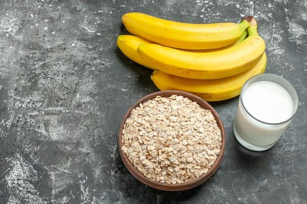Vista superior do plano de fundo do café da manhã com farelo de aveia orgânica em uma panela de leite de madeira marrom em um pacote de bananas de vidro em fundo escuro